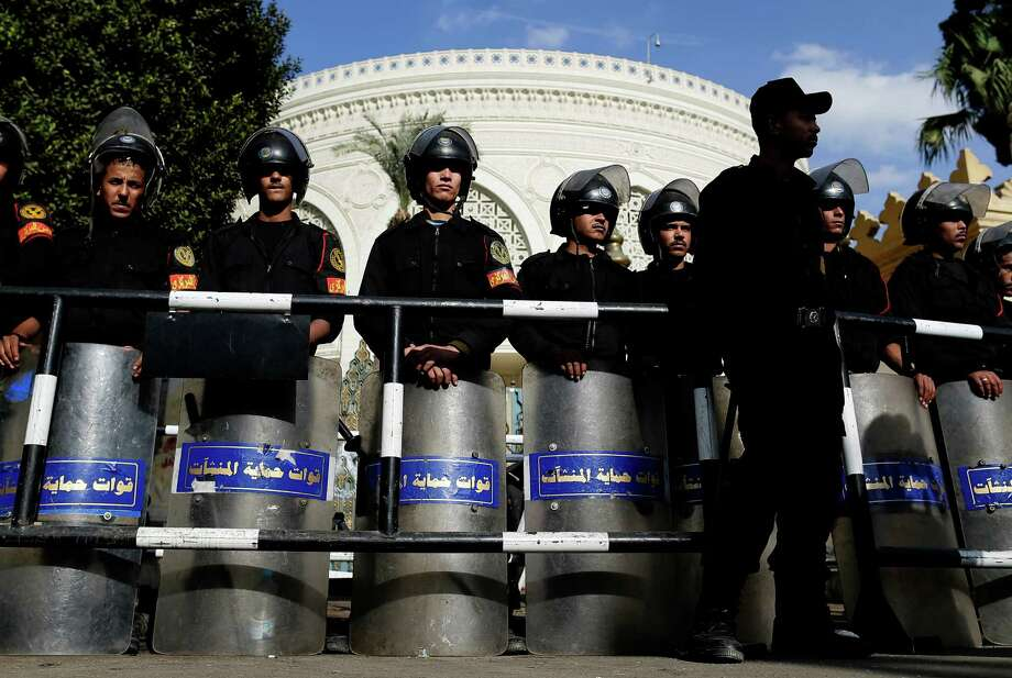 Egyptian riot policemen on Saturday guard a gate of the presidential palace amid ongoing protests in Cairo. Egypt's military appears to be supporting embattled President Mohammed Morsi. Photo: Hassan Ammar, STF / AP
