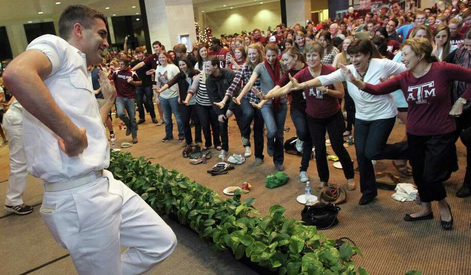 "Senior Yell Leader Drew Nelson teachs the crowd a new ""Heisman"" cheer, as they wait at a Heisman Trophy watch party for Texas A&M quarterback Johnny Manziel, on the A&M campus in College Station, Texas, on Saturday, Dec. 8, 2012. Manziel won the Heisman later Saturday in New York. (AP Photo/The Dallas Morning News, Louis DeLuca) MANDATORY CREDIT  NO SALES  MAGS OUT  TV OUT  INTERNET: AP MEMBERS ONLY Photo: Louis DeLuca, Associated Press / The Dallas Morning News"