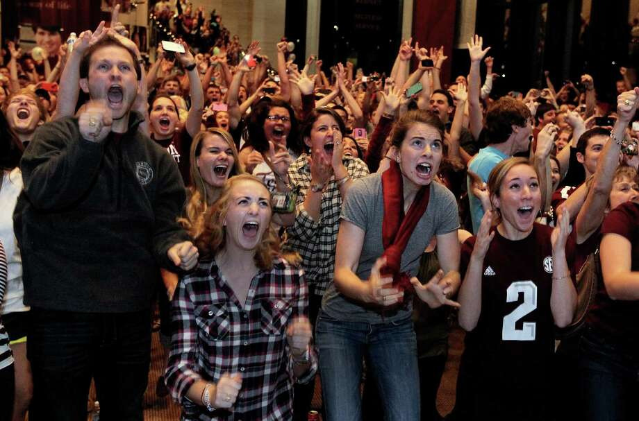 Texas A&M students Kyle Jackson, Erin Evetts, Sam Specchio and Kayla Mauch, from left, react to the announcement of Texas A&M quarterback Johnny Manziel winning the Heisman Trophy in New York, during the watch party on the A&M campus in College Station, Texas, on Saturday, Dec. 8, 2012. (AP Photo/The Dallas Morning News, Louis DeLuca) MANDATORY CREDIT  NO SALES  MAGS OUT  TV OUT  INTERNET: AP MEMBERS ONLY Photo: Louis DeLuca, Associated Press / The Dallas Morning News