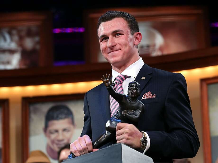 Texas A&M quarterback Johnny Manziel's initial Heisman pose comes with a smile as he clutches the trophy after becoming the first freshman to win the award. Photo: Handout, Getty Images For The Heisman Tru