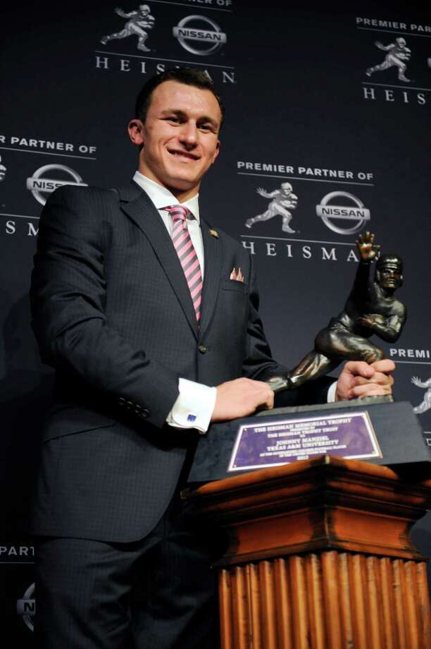 Texas A&M quarterback Johnny Manziel poses with the Heisman Trophy after becoming the first freshman to win the college football award, Saturday, Dec. 8, 2012, in New York. (AP Photo/Henny Ray Abrams) Photo: Henny Ray Abrams, Associated Press / FR151332 AP