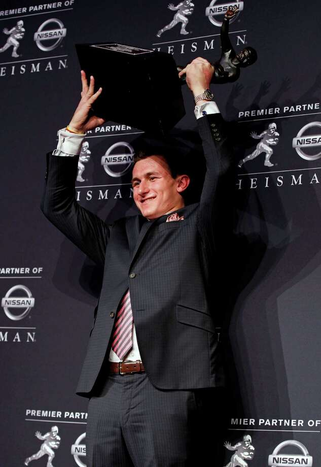 NEW YORK, NY - DECEMBER 08:  Quarterback Johnny Manziel of the Texas A&M University Aggies hoist the Heisman Memorial Trophy after being named the 78th Heisman Memorial Trophy Award winner at a press conference after the 78th Heisman Trophy Presentation at the Marriott Marquis on December 8, 2012 in New York City. Photo: Mike Stobe, Getty Images / 2012 Getty Images