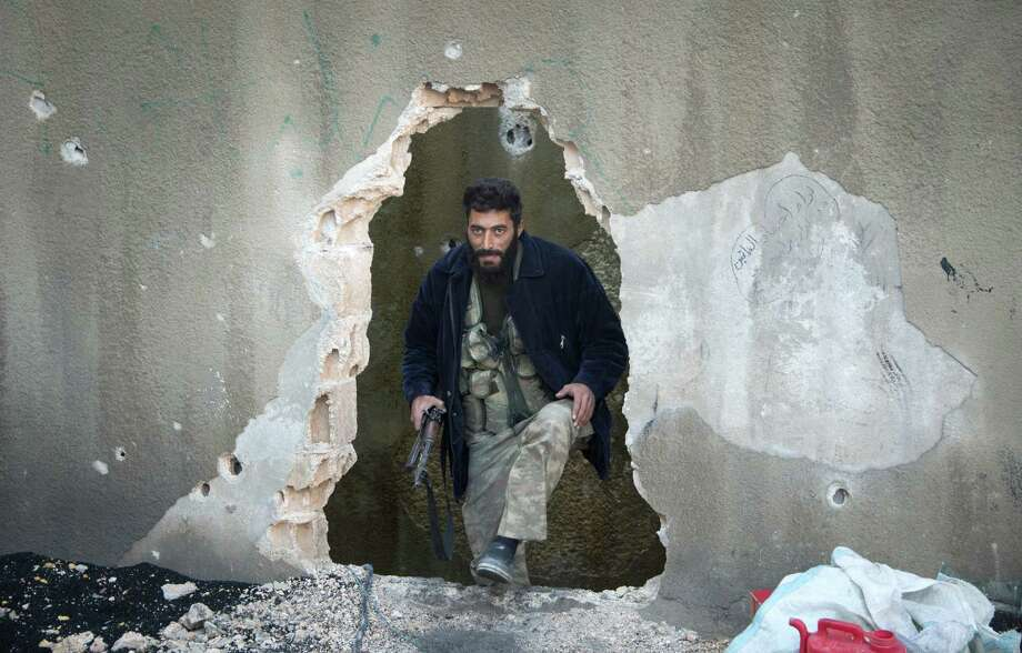 A Syrian rebel fighter emerges from behind a wall on the frontline in an Aleppo neighborhood. Fighters from a key group tied to al-Qaida in Iraq are gaining a foothold among rebels, much to the chagrin of the U.S. Photo: ODD ANDERSEN, Staff / AFP ImageForum