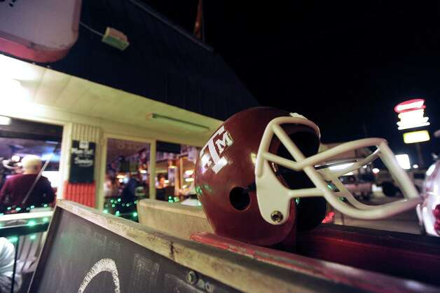 A Texas A&M helmet adorns the Wing King restaurant in Kerrville, Texas, where fans gathered for a Heisman Trophy announcement watch party on Saturday night, Dec. 8, 2012. Johnny Manziel, who played high school football for Tivy High School in Kerrville, won the Heisman trophy. Photo: Billy Calzada, Express-News / SAN ANTONIO EXPRESS-NEWS