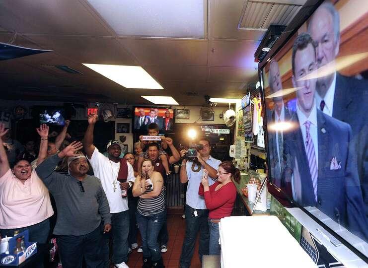 Fans of Texas A&M quarterback Johnny Manziel watch as Manziel accepts the Heisman trophy on televiso