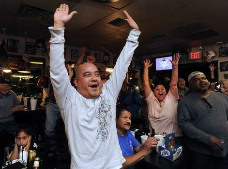 Joey Lopez, middle, and other fans of Texas A&M quarterback Johnny Manziel celebrate as the announcement is made on television at the Wing King restaurant in Kerrville that Manziel has won the Heisman trophy on Saturday night, Dec. 8, 2012. Manziel played high school football for Tivy High School in Kerrville. Photo: Billy Calzada, Express-News / SAN ANTONIO EXPRESS-NEWS
