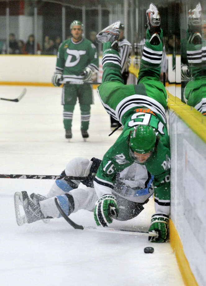 Danbury's Leland Fidler falls over Cape Cod's George Nicholes during their game at Danbury Ice Arena on Saturday, Dec. 8, 2012. Photo: Jason Rearick / The News-Times
