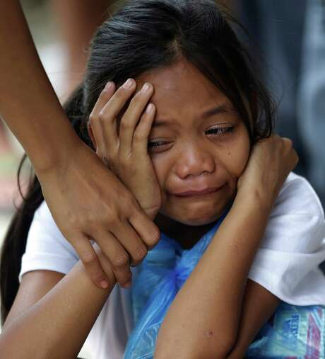 A girl grieves Saturday upon seeing the coffin of a relative at a morgue in New Bataan, Philippines. Photo: Bullit Marquez, STF / AP
