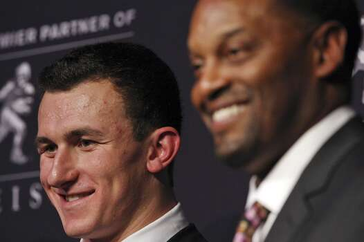 Texas A&M's quarterback Johnny Manziel, the 2012 Heisman Trophy winner, (left) and Texas A&M's headcoach Kevin Sumlin  answers questions from the media during a press conference Saturday Dec. 8, 2012 at the New York Marriott Marquis hotel in New York, New York.