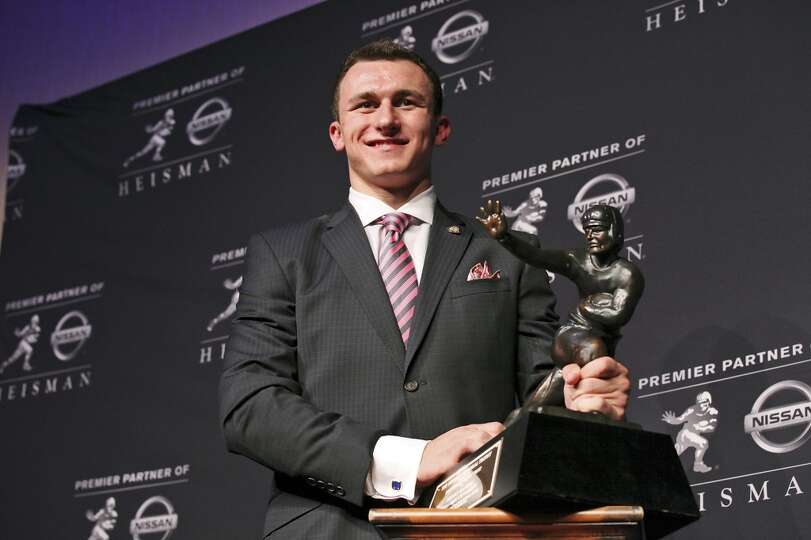 Texas A&M's quarterback Johnny Manziel, the 2012 Heisman Trophy winner, poses for photos during a pr