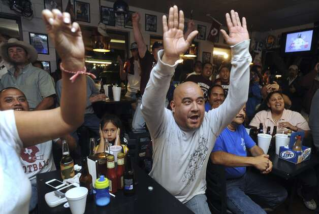 Joey Lopez, middle, and other fans of Texas A&M quarterback Johnny Manziel celebrate as the announcement is made on television at the Wing King restaurant in Kerrville that Manziel has won the Heisman trophy on Saturday night, Dec. 8, 2012. Manziel played high school football for Tivy High School in Kerrville.