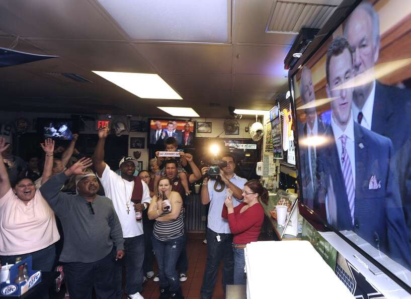 Fans of Texas A&M quarterback Johnny Manziel watch as Manziel accepts the Heisman trophy on televiso