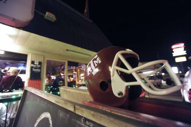 A Texas A&M helmet adorns the Wing King restaurant in Kerrville, Texas, where fans gathered for a Heisman Trophy announcement watch party on Saturday night, Dec. 8, 2012. Johnny Manziel, who played high school football for Tivy High School in Kerrville, won the Heisman trophy.
