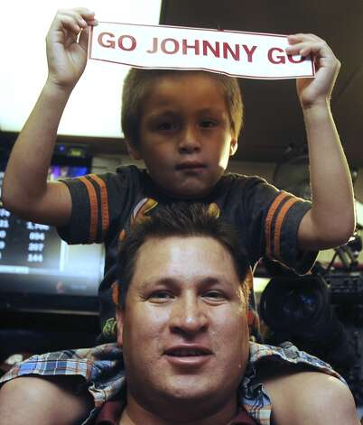Tony Castillo and son, Jaden, show their enthusiasm for Johnny Manziel, Texas A&M quarterback who won the Heisman trophy, on Saturday, Dec. 8, 2012. Fans in Kerrville, where Manziel played high school football, gathered at the Wing King restaurant.
