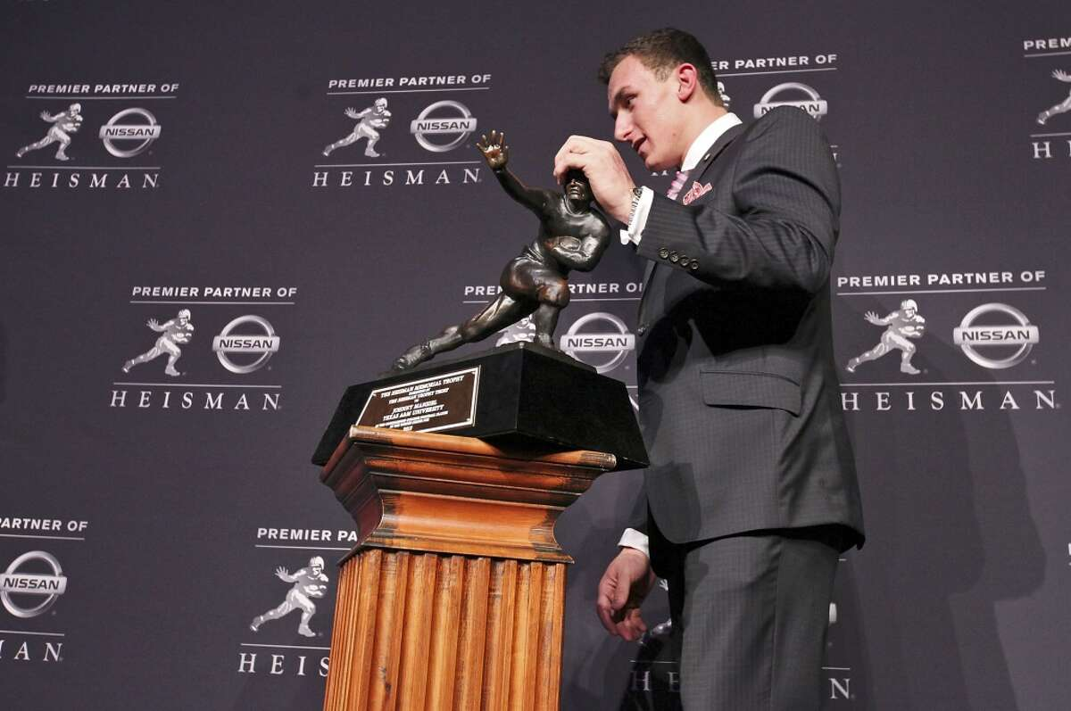 Texas A&M's quarterback Johnny Manziel, the 2012 Heisman Trophy winner, grabs the trophy while posing for photos during a press conference Saturday Dec. 8, 2012 at the New York Marriott Marquis hotel in New York, New York.
