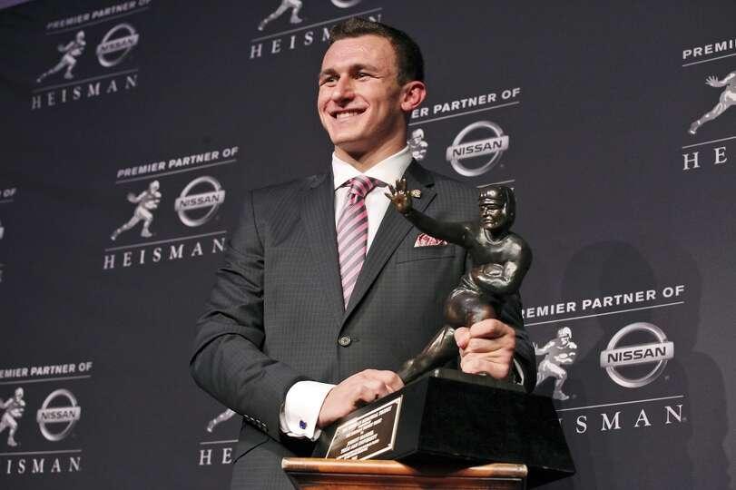 Texas A&M's quarterback Johnny Manziel, the 2012 Heisman Trophy winner, poses for photos during a pr