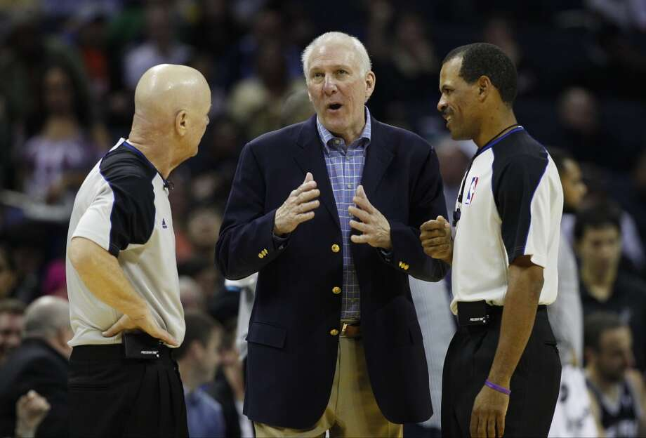 San Antonio Spurs head coach Gregg Popovich, center, argues a call with referee Joe Crawford, left, and Eric Lewis, right, during the second half of an NBA basketball game in Charlotte, N.C., Saturday, Dec. 8, 2012. The Spurs won 132-102. (AP Photo/Chuck Burton) (Associated Press)