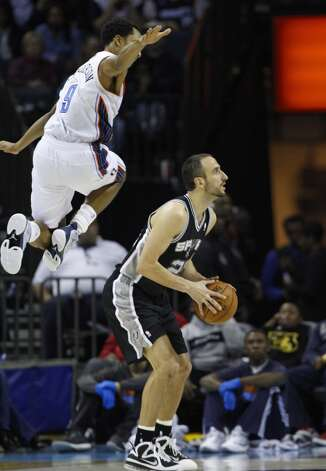 Charlotte Bobcats' Gerald Henderson, top, sails high as he tries to block a shot by San Antonio Spurs' Manu Ginobili, right, during the second half of an NBA basketball game in Charlotte, N.C., Saturday, Dec. 8, 2012. The Spurs won 132-102. (AP Photo/Chuck Burton) (Associated Press)