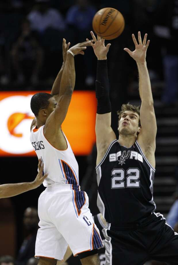 Charlotte Bobcats' Ramon Sessions, left, tries to shoot over San Antonio Spurs' Tiago Splitter, right, during the first half of an NBA basketball game in Charlotte, N.C., Saturday, Dec. 8, 2012. (AP Photo/Chuck Burton) (Associated Press)