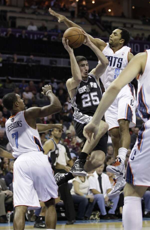 San Antonio Spurs' Nando de Colo, center, looks to pass as he is trapped by Charlotte Bobcats' Ramon Sessions, left, and Gerald Henderson, right, during the first half of an NBA basketball game in Charlotte, N.C., Saturday, Dec. 8, 2012. (AP Photo/Chuck Burton) (Associated Press)