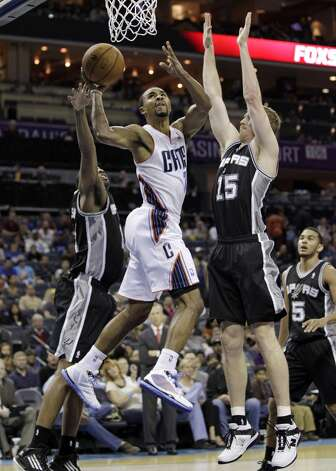 Charlotte Bobcats' Ramon Sessions (7) drives between San Antonio Spurs' Matt Bonner, right, and James Anderson, left, during the second half of an NBA basketball game in Charlotte, N.C., Saturday, Dec. 8, 2012. The Spurs won 132-102. (AP Photo/Chuck Burton) (Associated Press)