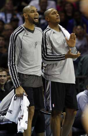 San Antonio Spurs' Tim Duncan, left, and Boris Diaw, right, cheer their teammates against the Charlotte Bobcats during the second half of an NBA basketball game in Charlotte, N.C., Saturday, Dec. 8, 2012. The Spurs won 132-102. (AP Photo/Chuck Burton) (Associated Press)