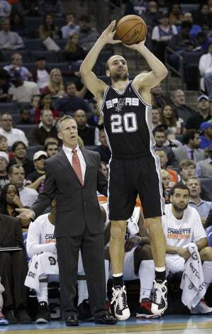 San Antonio Spurs' Manu Ginobili (20) shoots as Charlotte Bobcats head coach Mike Dunlap looks on during the first half of an NBA basketball game in Charlotte, N.C., Saturday, Dec. 8, 2012. (AP Photo/Chuck Burton) (Associated Press)