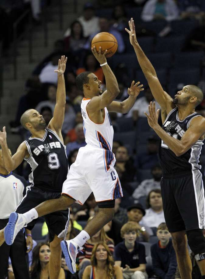 Charlotte Bobcats' Ramon Sessions, center, tries to shoot between San Antonio Spurs' Tony Parker, left, and Tim Duncan, right, during the second half of an NBA basketball game in Charlotte, N.C., Saturday, Dec. 8, 2012. The Spurs won 132-102. (AP Photo/Chuck Burton) (Associated Press)