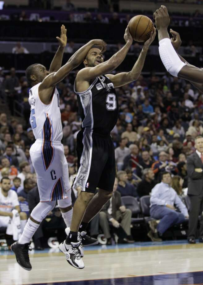 San Antonio Spurs' Tony Parker (9) is fouled as he drives past Charlotte Bobcats' Kemba Walker (15) during the first half of an NBA basketball game in Charlotte, N.C., Saturday, Dec. 8, 2012. (AP Photo/Chuck Burton) (Associated Press)