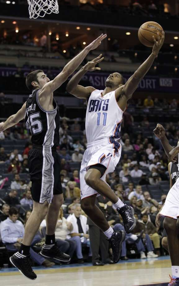 Charlotte Bobcats' Cory Higgins (11) drives to the basket as San Antonio Spurs' Nando de Colo (25) defends during the second half of an NBA basketball game in Charlotte, N.C., Saturday, Dec. 8, 2012. The Spurs won 132-102. (AP Photo/Chuck Burton) (Associated Press)
