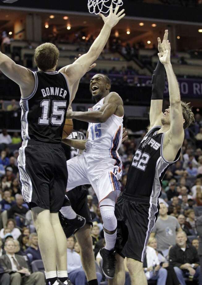 Charlotte Bobcats' Kemba Walker (15) drives between San Antonio Spurs' Tiago Splitter (22) and Matt Bonner (15) during the second half of an NBA basketball game in Charlotte, N.C., Saturday, Dec. 8, 2012. The Spurs won 132-102. (AP Photo/Chuck Burton) (Associated Press)