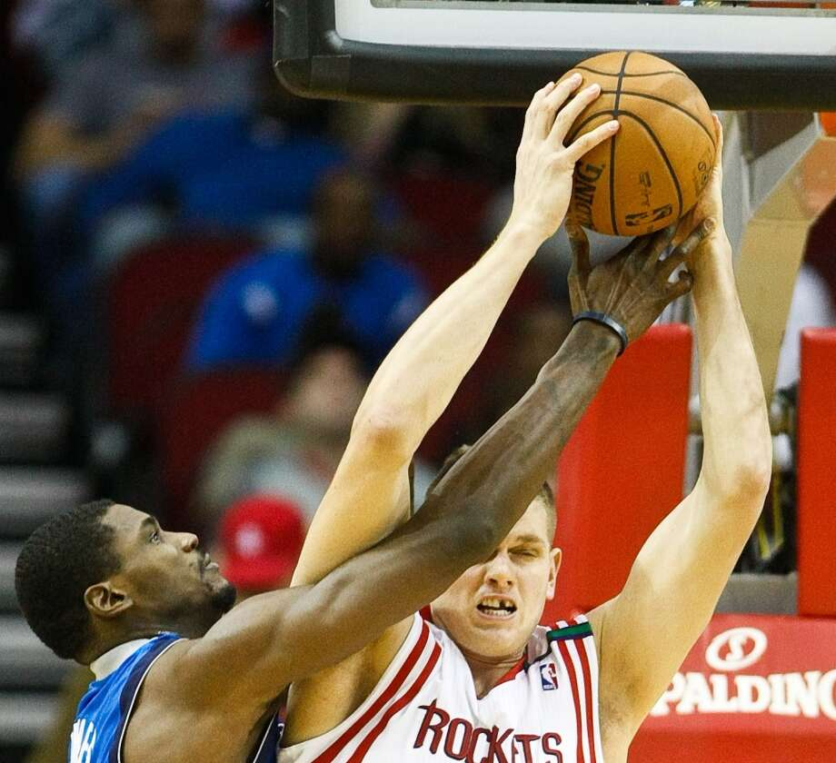 Mavericks center Bernard James and Rockets center Cole Aldrich fight for a rebound. (Nick de la Torre  / Houston Chronicle)