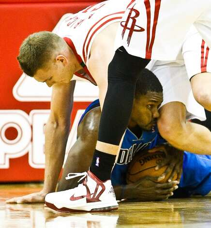 Mavericks center Bernard James gets kicked in the face by Rockets center Cole Aldrich as the two scramble for a loose ball. (Nick de la Torre  / Houston Chronicle)