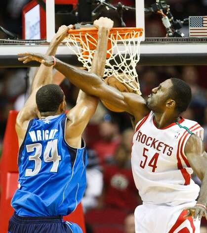 Mavericks center Brandan Wright dunks the ball as Rockets power forward Patrick Patterson tries to stop him. (Nick de la Torre  / Houston Chronicle)