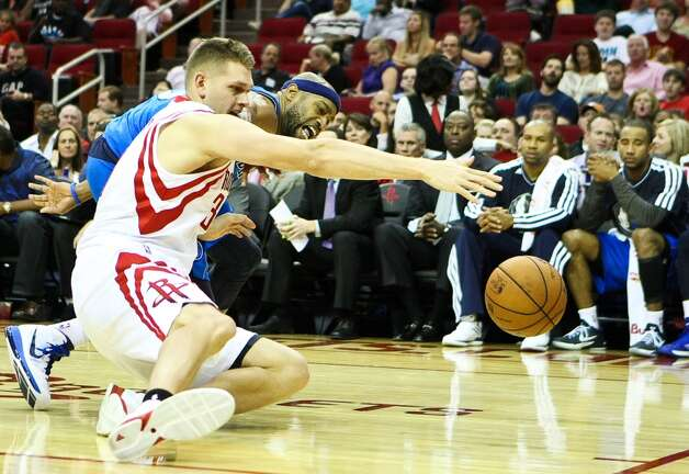 Rockets center Cole Aldrich and Mavericks shooting guard Vince Carter fight for a lose ball. (Nick de la Torre  / Houston Chronicle)