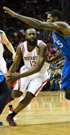 Rockets shooting guard James Harden is defended close by the Mavericks' defense. (Nick de la Torre  / Houston Chronicle)