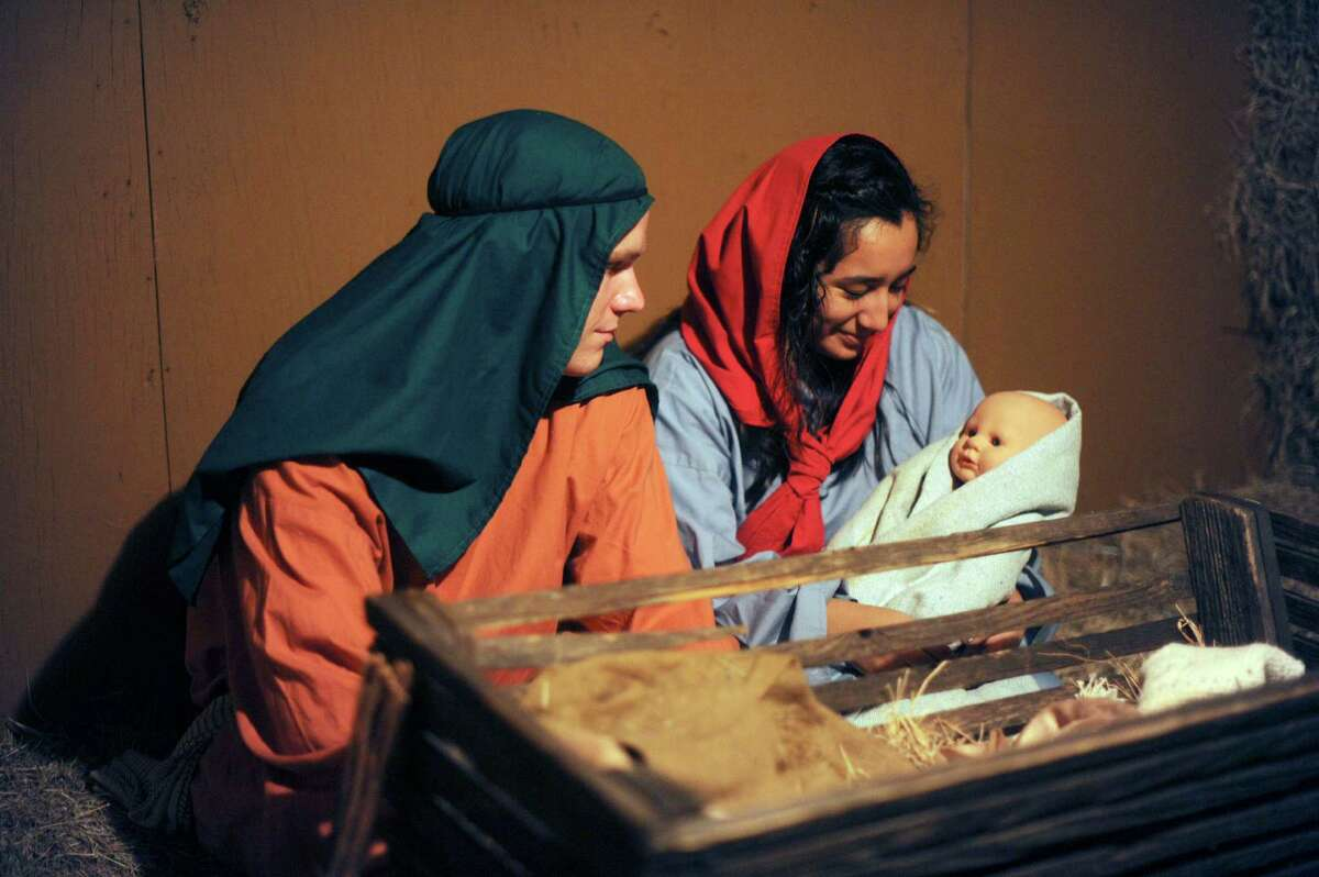 Aubrey Rodriguez as Mary and Brady Moore as Joseph hold a doll representing the Christ child during in a living replica of Bethlehem called