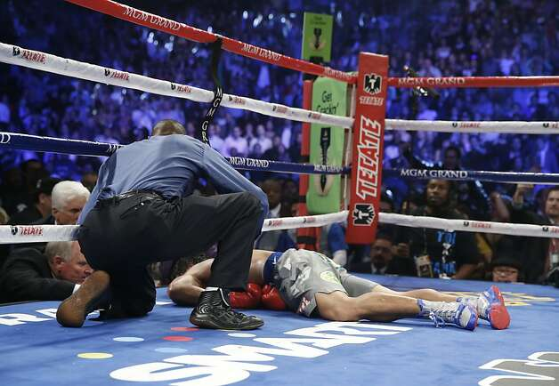 Manny Pacquiao, from the Philippines, lies on the canvas as referee Kenny Bayless kneels nearby after being knocked out by Juan Manuel Marquez, from Mexico, in the sixth round of their WBO world welterweight  fight Sunday, Dec. 9, 2012, in Las Vegas. (AP Photo/Eric Jamison) Photo: Eric Jamison, Associated Press