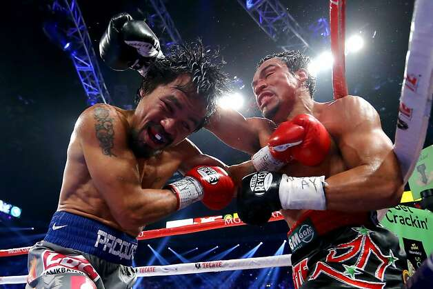 LAS VEGAS, NV - DECEMBER 08:  (L-R) Manny Pacquiao and Juan Manuel Marquez exchange blows during their welterweight bout at the MGM Grand Garden Arena on December 8, 2012 in Las Vegas, Nevada.  (Photo by Al Bello/Getty Images) Photo: Al Bello, Getty Images