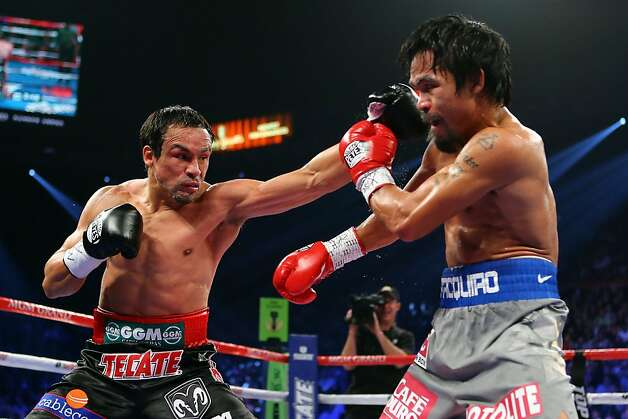 LAS VEGAS, NV - DECEMBER 08:  (L-R) Juan Manuel Marquez throws a left to the face of Manny Pacquiao during their welterweight bout at the MGM Grand Garden Arena on December 8, 2012 in Las Vegas, Nevada.  (Photo by Al Bello/Getty Images) Photo: Al Bello, Getty Images