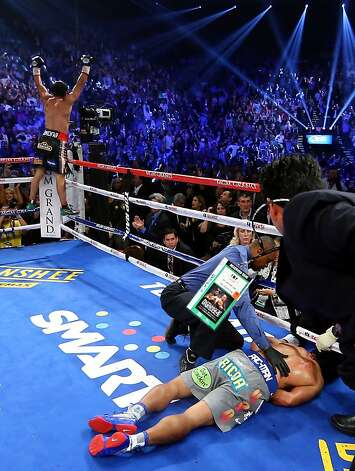 LAS VEGAS, NV - DECEMBER 08:  Manny Pacquiao lays face down on the mat after being knocked out in the sixth round as Juan Manuel Marquez celebrates during their welterweight bout at the MGM Grand Garden Arena on December 8, 2012 in Las Vegas, Nevada.  (Photo by Al Bello/Getty Images) Photo: Al Bello, Getty Images