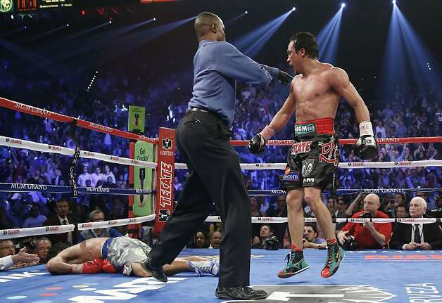 With Manny Pacquiao down and out, Juan Manuel Marquez is directed to his corner. Photo: Eric Jamison, Associated Press