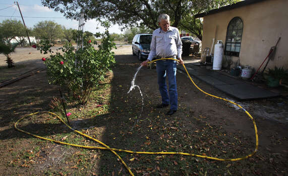 Rudy Rizo, a resident of Pueblo Nuevo, a colonia just outside Eagle Pass, waters the roses in his side yard, Thursday, Nov. 29, 2012. Rudy Heredia, Commissioner of Precinct 2, and several county employees have been indicted for misuse of grant funds, among other charges.  Many of the streets in Pueblo Nuevo remain unpaved. Photo: Bob Owen, San Antonio Express-News / © 2012 San Antonio Express-News