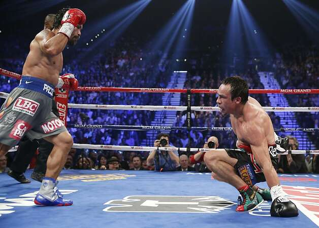 Manny Pacquiao, from the Philippines, left, sends Juan Manuel Marquez, from Mexico, to the mat in the fifth round of their WBO world welterweight  fight Saturday, Dec. 8, 2012, in Las Vegas. Marquez went on to win the bout by a knockout. (AP Photo/Eric Jamison) Photo: Eric Jamison, Associated Press