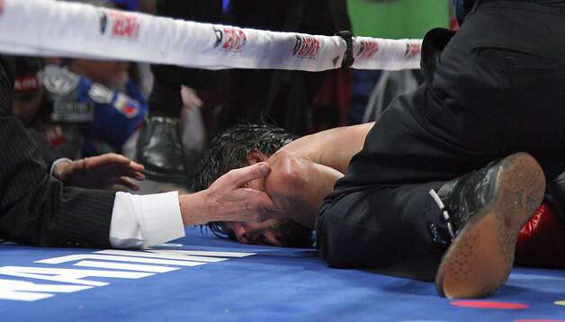 Hands reach in ringside to support the head of Manny Pacquiao after he was knocked out by Juan Manuel Marquez on December 8, 2012, at the MGM Grand Garden in Las Vegas, Nevada.  AFP PHOTO / John GurzinskiJOHN GURZINSKI/AFP/Getty Images Photo: John Gurzinski, AFP/Getty Images