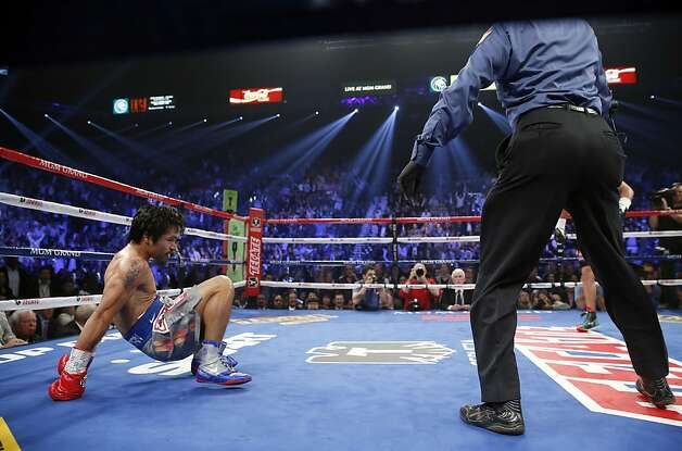 Manny Pacquiao, from the Philippines, lifts himself from the canvas as referee Kenny Bayless stands by after being knocked down in the third round of his WBO world welterweight fight against Juan Manuel Marquez, from Mexico,  Saturday, Dec. 8, 2012, in Las Vegas. (AP Photo/Eric Jamison) Photo: Eric Jamison, Associated Press