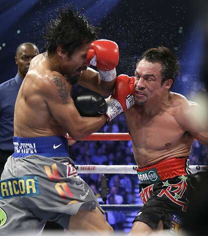 Juan Manuel Marquez, from Mexico, right, and Manny Pacquiao, from the Philippines, trade blows during their WBO world welterweight  fight Saturday, Dec. 8, 2012, in Las Vegas. Marquez won the fight by a knockout. Referee Kenny Bayless looks on at left. (AP Photo/Julie Jacobson) Photo: Julie Jacobson, Associated Press