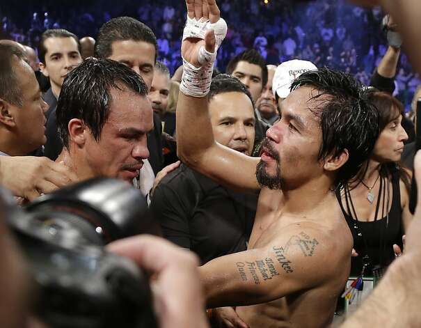 Manny Pacquiao, from the Philippines, right, stands in the ring with Juan Manuel Marquez, from Mexico, after losing by a knockout in their WBO world welterweight  fight Saturday, Dec. 8, 2012, in Las Vegas. (AP Photo/Julie Jacobson) Photo: Julie Jacobson, Associated Press