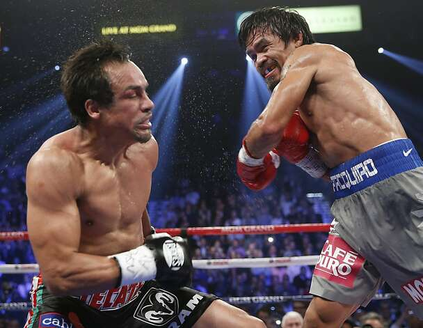 Manny Pacquiao, from the Philippines, connects against Juan Manuel Marquez, from Mexico, during their WBO world welterweight  fight Saturday, Dec. 8, 2012, in Las Vegas. Marquez won by a knockout. (AP Photo/Eric Jamison) Photo: Eric Jamison, Associated Press