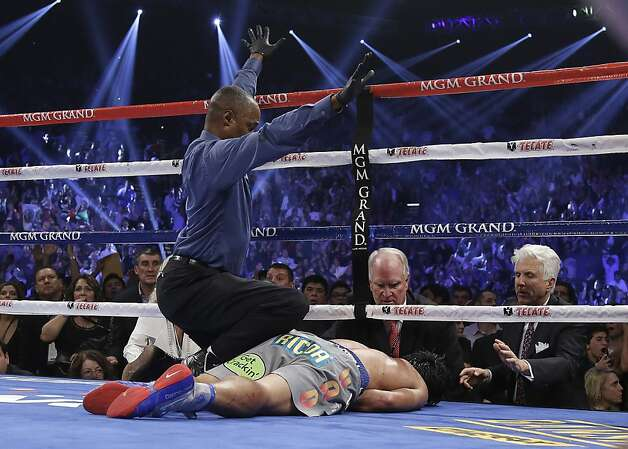Referee Kenny Bayless calls the fight as he kneels over Manny Pacquiao, from the Philippines, after he was knocked out by Juan Manuel Marquez, from Mexico, during their WBO world welterweight  fight Saturday, Dec. 8, 2012, in Las Vegas. (AP Photo/Julie Jacobson) Photo: Julie Jacobson, Associated Press